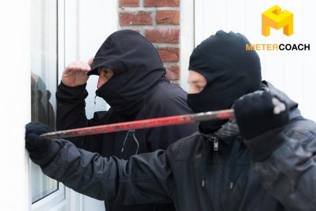 Einbrecher öffnen Fenster einer Immobilie mit einem Brecheisen