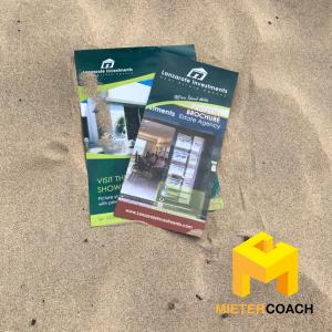 Broschüren im Sand: Infobroschüre der Immobilienagentur Lanzarote Investments